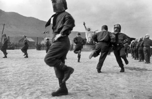 "Werner Bischof  ""South Korea, Island of Koje Do, 1952""Internment camp for North Korean prisoners of war. The prisoners perform a square dance in front of a large Statue of Liberty."